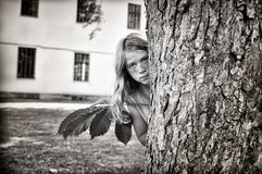 Girl sneaking behind a tree Stock Photo