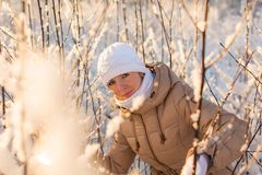 Girl sneaks in a winter forest. Young girl sneaks in a winter forest Stock Photography