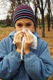 Girl sneasing in handkerchief Stock Photos