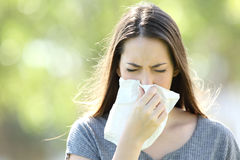 Girl sneezing and blowing in a wipe. Front view of a single girl sneezing and blowing in a wipe outdoors with a green background royalty free stock image