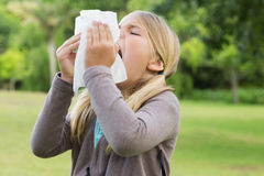Girl sneezing into tissue paper at park Royalty Free Stock Image
