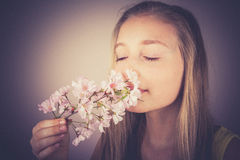 Girl sniff cherry blossoms, grain effect Stock Photo