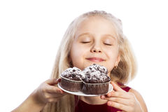 Girl sniffing chocolate muffins Royalty Free Stock Images