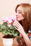 Girl sniffing flowers cyclamen Royalty Free Stock Image