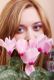 Girl sniffing flowers cyclamen Royalty Free Stock Images