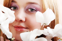 Girl sniffing flowers cyclamen Royalty Free Stock Photography