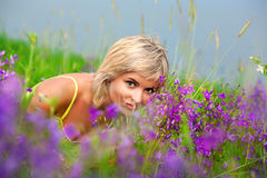 Girl sniffing flowers in the meadow Stock Image