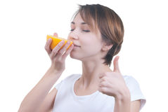 Girl sniffing half of grapefruit Stock Photography