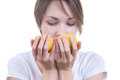 Girl sniffing two parts of lemon royalty free stock photos