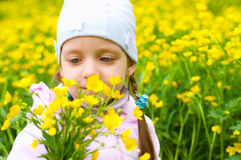 Girl sniffing yellow flowers. Lovely girl sniffing yellow flowers in the meadow Stock Image