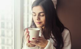 Girl Sniffs Coffee. Beautiful girl wears white bathrobe smells cup of coffee sitting on the windowsill near window stock photos