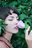 Girl sniffs a flower Royalty Free Stock Photography