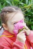 Girl Sniffs a Flower Stock Photo