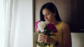 Girl sniffs flowers. A beautiful white girl brings a bouquet of peonies to her face and inhales their scent, then looks stock footage