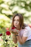 Girl sniffs a red flower.teenager girl smelling roses. In the Park in a pink t-shirt stock images