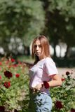 Girl sniffs a red flower.teenager girl smelling roses stock photo