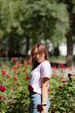 Girl sniffs a red flower.teenager girl smelling roses. In the Park in a pink t-shirt royalty free stock photography