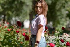 Girl sniffs a red flower.teenager girl smelling roses. In the Park in a pink t-shirt stock photo