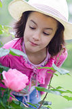 Girl sniffs the roses Stock Image