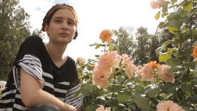 Girl sniffs roses in the park stock footage
