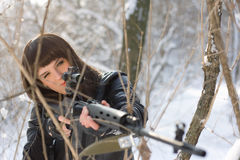 Girl with a sniper rifle. Portrait of girl with a sniper rifle in winter forest Royalty Free Stock Photography