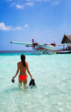 Girl with snorkeling gear in front of a seaplane. In the Maldives Stock Photo