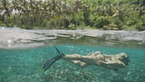 Girl Snorkeling Reef Indonesia Tropic Underwater Slowmotion. Beautiful underwater 50/50 footage of a girl snorkeling in a shalow bay in Nusa Penida, Indonesia stock video