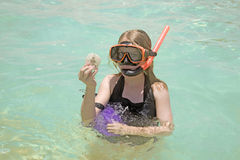 Girl snorkeling with sand dollar. A girl in the ocean snorkeling while holding a sand dollar Stock Photo