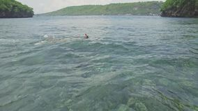 Girl Snorkeling Top Reef Shallow Water Tropical Coral Aerial 4k. Aerial footage of a girl snorkeling in a shallow water bay in Nusa Penida, Indonesia stock video footage