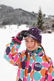 Girl in the snow. A girl brushing snow off her hat in the snow Stock Images
