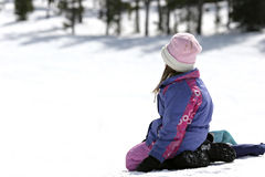 Girl in snow. Girl sitting in the snow, watching and waiting Stock Photo