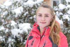 The girl in the snow. Beautiful girl with long hair in a red jacket in the snow near the greenery Royalty Free Stock Images