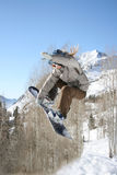 Girl snow boarder hits jump Stock Photos