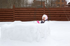 Girl in snow fortress playing snowballs Royalty Free Stock Photo