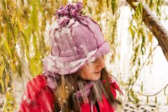 Girl with snow on the head under the tree Royalty Free Stock Photos
