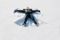 Girl in the snow making angel Stock Image
