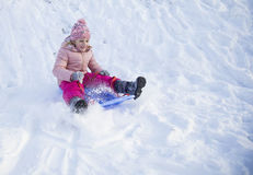 Girl on snow slides in winter time Royalty Free Stock Image