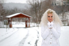 Girl in snow trembling. Blonde girl in white jacket trembling Stock Photo
