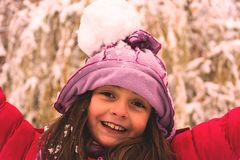 Girl and Snowball fight. Girl with a snowball on the head. Snowball  suddenly hit in the head. She is happy and plays Stock Image