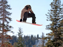 Girl on a snowboard. Teen girl jumping high on a snowboard royalty free stock photo