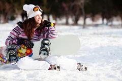Girl with snowboard. Sitting on the snow stock photos
