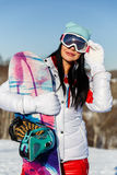 Girl with snowboard and glasses Royalty Free Stock Photo