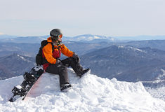 Girl with snowboard on top of mountain Stock Image