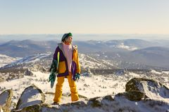 Girl with snowboard on top of the mountain stock photography