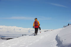 Girl with a snowboard walks away along the slope Royalty Free Stock Photo