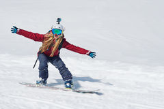 Girl snowboarder goes quickly down the slope and shouts Stock Image