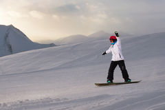 Girl snowboarder rides down  slope Royalty Free Stock Images