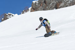 Girl snowboarder rides steep mountains. Kamchatka, Far East, Russia. KAMCHATKA, RUSSIA - MARCH 9, 2014: Girl snowboarder rides steep mountains. Competitions Royalty Free Stock Photography