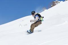 Girl snowboarder rides steep mountains. Kamchatka, Far East, Russia Royalty Free Stock Photo