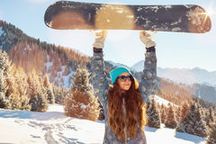 Girl snowboarder standing on a mountain top keeps, snowboard over the head Stock Image